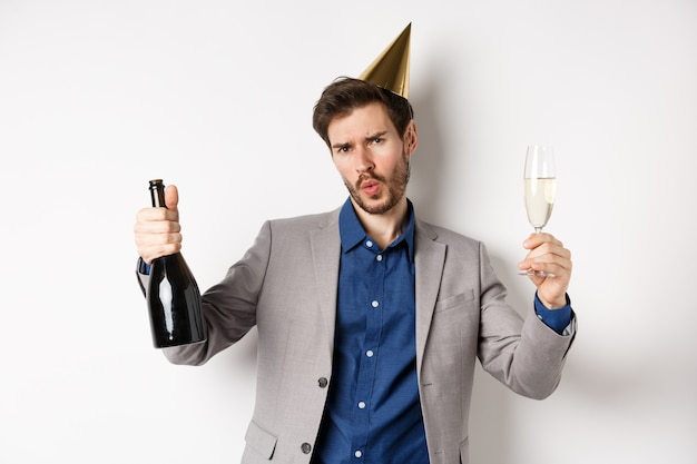 Viering en vakantie concept. gelukkig man in pak plezier op feestje, verjaardag hoed dragen, dansen met champagne en alcohol drinken.