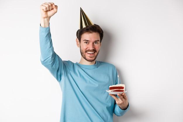 Viering en vakantie concept. gelukkig man viert verjaardag in feestmuts, bday cake houden en hand opsteken in triomf, staande op witte achtergrond.