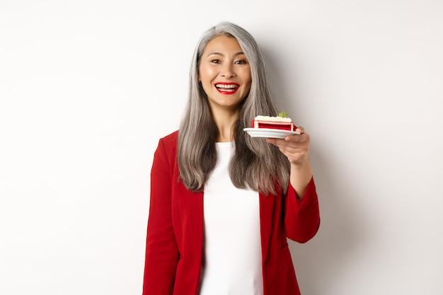 Viering en vakantie concept. glimlachende aziatische zakenvrouw feliciteert werknemers, geeft een bord met zoete cake en ziet er gelukkig uit, staande op een witte achtergrond