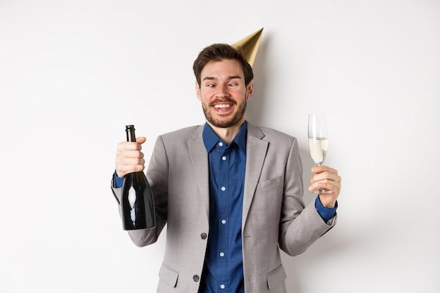 Viering en vakantie concept. grappige dronken man in pak en verjaardagshoed, ogen loensen en plezier hebben op feestje, champagne drinken, witte achtergrond.