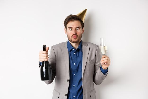 Viering en vakantie concept. grappige dronken man in pak en verjaardagshoed