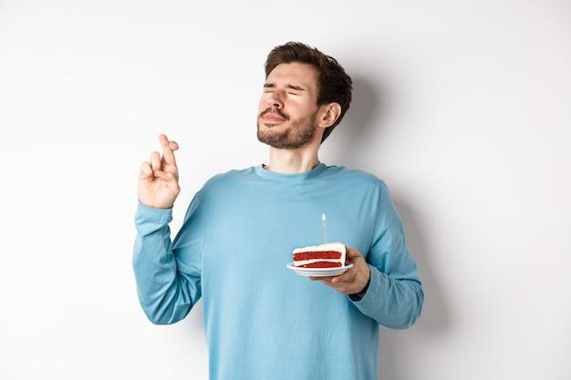 Viering en vakantie concept. knappe jongeman viert verjaardag, wens met bday cake in de hand, staande op witte achtergrond.
