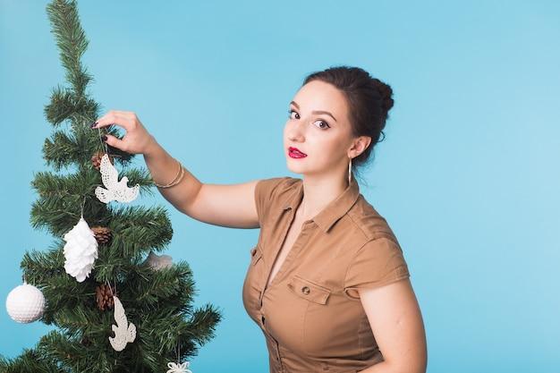 Viering en vakantie concept - portret van lachend meisje met kerstboom over blauwe muur.