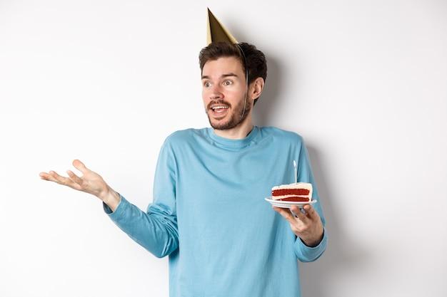 Viering en vakantie concept. verrast man schouderophalend in ongeloof, wegkijken, verjaardagstaart vasthouden en feestkegel hoed, witte achtergrond dragen.