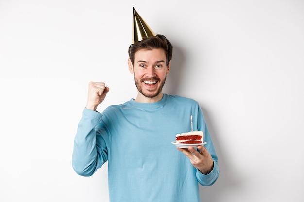 Viering en vakantie concept. vrolijke jongeman viert verjaardag in feestmuts, bday cake vasthouden en er gelukkig uitzien, staande op een witte achtergrond.