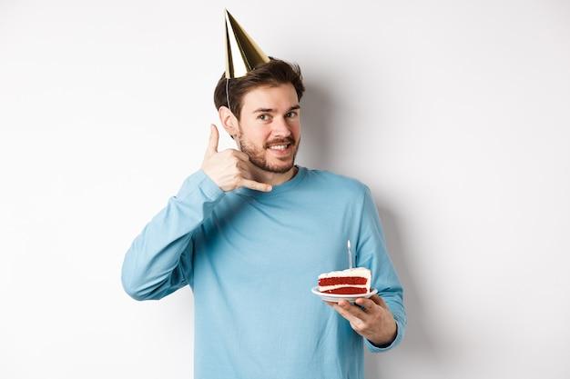Viering en vakantie concept. vrolijke lachende man in feestmuts, verjaardag vieren met bday cake, bel me telefoongebaar in de buurt van oor, witte achtergrond weergegeven: