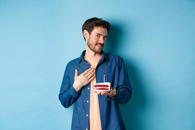 Viering en vakantieconcept. aangeraakt en gevleid man met verjaardagstaart en borst dankbaar aan te raken, staande op een blauwe achtergrond.