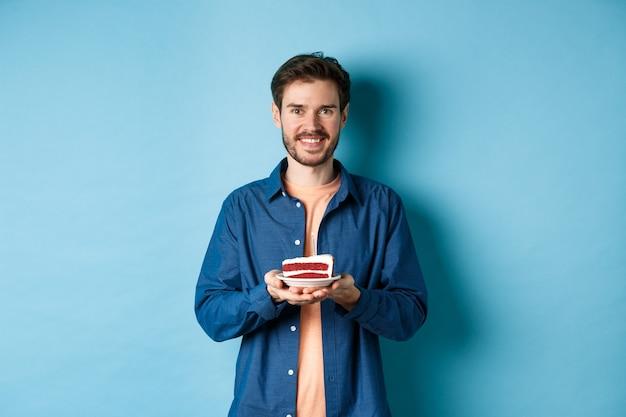 Viering en vakantieconcept. glimlachende man met verjaardagstaart met kaars en op zoek gelukkig, staande op blauwe achtergrond.