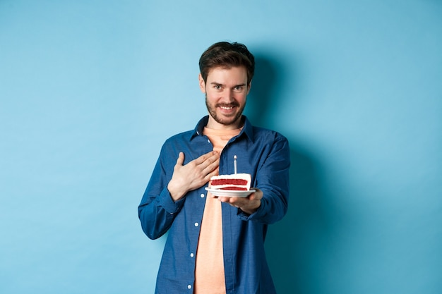 Viering en vakantieconcept. man blozen en gelukkige verjaardag wensen, strekken b-dag cake uit met aangestoken kaars, staande op een blauwe achtergrond.