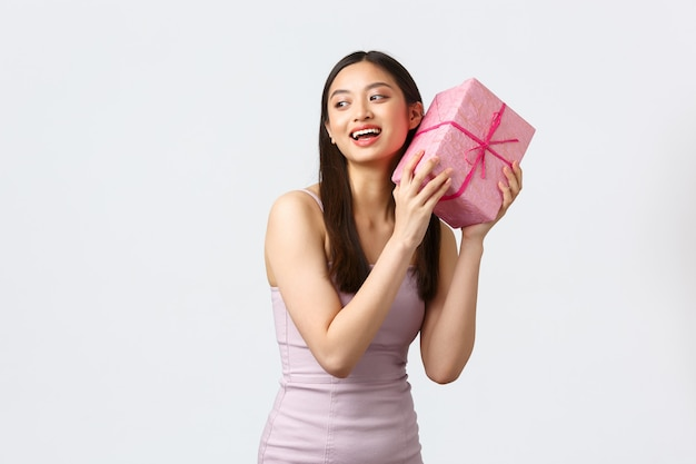 Viering, feest en vakantie concept. opgewonden gelukkig schattig aziatisch meisje in avondjurk, geschenkdoos schudden om te raden wat erin