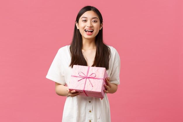 Viering, feestvakanties en leuk concept. gelukkig dankbaar schattig aziatisch meisje dat verjaardag viert, verjaardagscadeau ontvangt en bedankt, vrolijk glimlacht, staande roze achtergrond verrukt