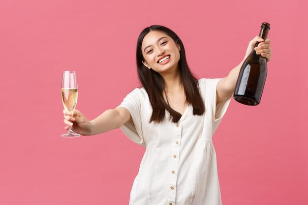 Viering, feestvakanties en leuk concept. gelukkige glimlachende aziatische vrouwengastheer van gebeurtenis, die flessenchampagne en glas houden en handen voor het koesteren van gast bereiken, die roze muur bevinden zich