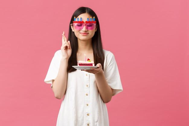 Viering, feestvakanties en leuk concept. glimlachend gelukkig verjaardagsmeisje dat wens doet op b-day cake, ogen sluiten en vingers gekruist veel geluk, droom die uitkomt, roze achtergrond.