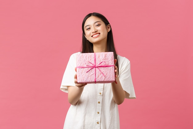 Viering, feestvakanties en leuk concept. vriendelijke mooie aziatische vriendin lacht, feliciteert vriend met verjaardag en geeft cadeau, staande roze achtergrond