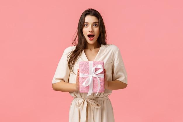 Viering, geluk en emoties concept. de vrolijke jonge vrouw ontvangt een aangenaam geschenk, houdt een ingepakt cadeau, hijgt verbaasd, open mond en zag er gefascineerd uit, roze achtergrond