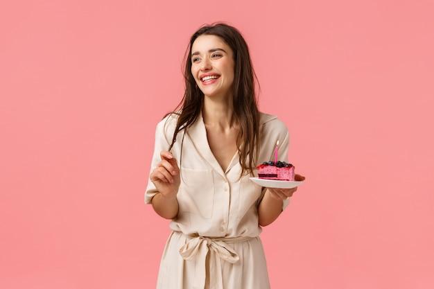 Viering, geluk en vakantie concept. mooie jonge vrouw plezier, houden plaat met cake, glimlachen en zorgeloos lachen, b-day dessert uitblazen kaars eten, plezier maken