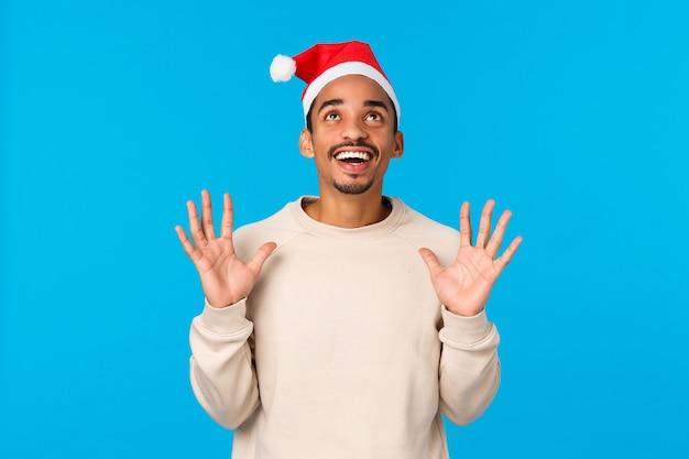 Viering, kerstsfeer en geluk concept. vrolijke en gelukkige afro-amerikaanse jonge man