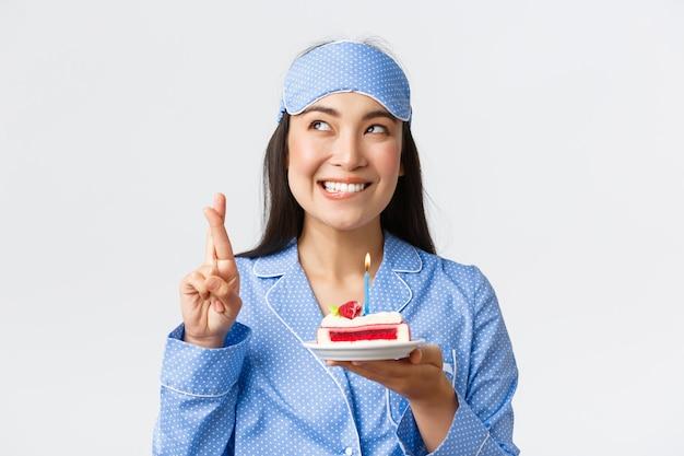 Viering, lifestyle en vakantie concept. hoopvol en dromerig lachende gelukkige aziatische vrouw in slaapmasker en pyjama, gefeliciteerd met verjaardag in bed, wens doen voordat kaars op taart blaast.