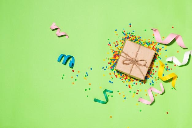 Viering plat leggen. geschenkdoos met kleurrijke feestartikelen op groene achtergrond.