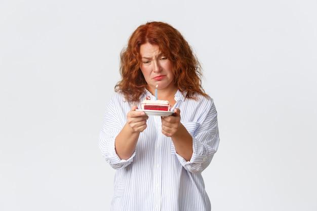 Viering, vakantie en emoties concept. ongemakkelijke en droevige roodharige vrouw van middelbare leeftijd haat haar verjaardag, kijkt boos naar verjaardagstaart met aangestoken kaars, voelt midlifecrisis, witte muur.