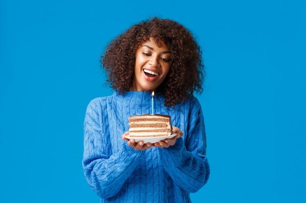 Viering, vakantie en feestconcept. dromerige en mooie schattige afro-amerikaanse vrouw met afro kapsel, in trui, kantelen hoofd en kijken naar verlichte kaars op verjaardagstaart, glimlachend wensend