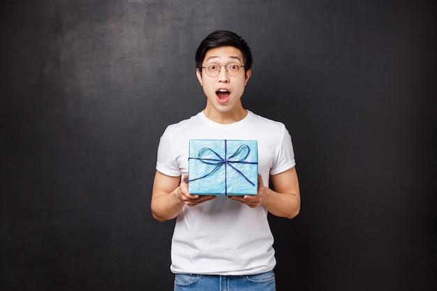 Viering, vakantie en lifestyle concept. verraste gelukkige jonge aziatische b-day kerel ontvangt leuk verpakt cadeau, houdt geschenkdoos hijgend en kijkt verbaasd, viert verjaardag