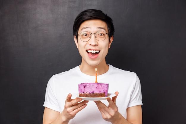 Viering, vakantie en verjaardag concept. close-up portret van verbaasd en gelukkig jonge aziatische man die b-day cake en lachend geamuseerd, partij gooien, kaars uitblazen voor het maken van wens
