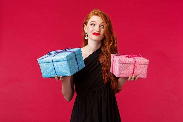 Viering, vakantie en vrouwen concept. portret van besluiteloze knappe roodharige vrouw in zwarte jurk, met twee geschenken in handen, wegkijken en grijnzend besluiteloos, weet niet wat geven