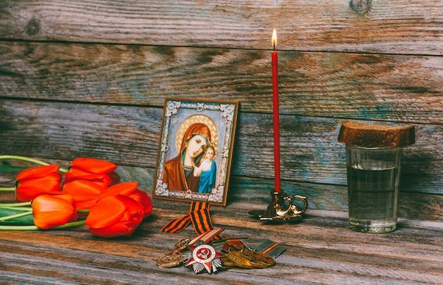 Viering van overwinningsdagmedailles, orthodoxe icoon en brandende rode kaars, boeket bloemen van rode tulpen en een glas wodka met een stuk roggebrood