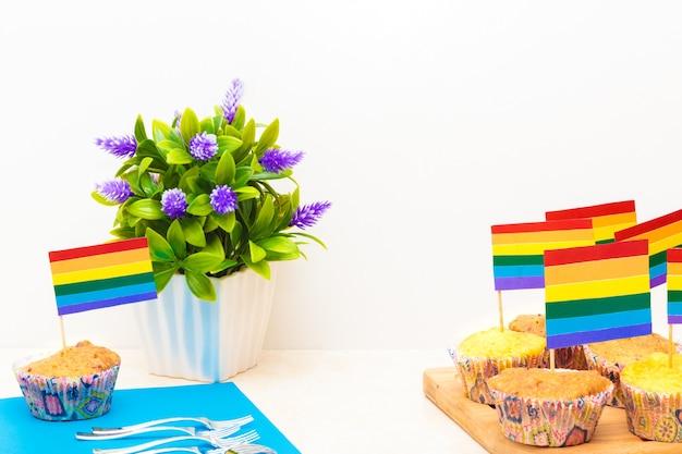 Viering van trotsdag met vlaggen op cupcakes, met een bloem in een pot op witte achtergrond on