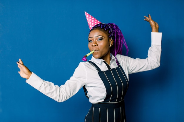 Viering, vrienden, vrijgezellenfeest, verjaardagsconcept - glimlachende afrikaanse amerikaanse vrouw die roze partijhoed dragen en gunsthoorn blazen