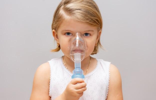 Vierjarig meisje met astma en allergieën maakt inademing in een masker met medicijnen via een vernevelaar op een grijze achtergrond