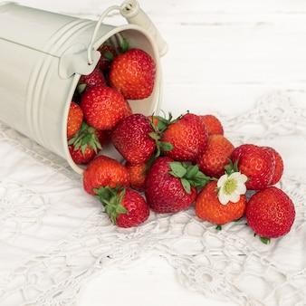 Vierkant. aardbeien op een witte houten oude achtergrond, gebreide servet