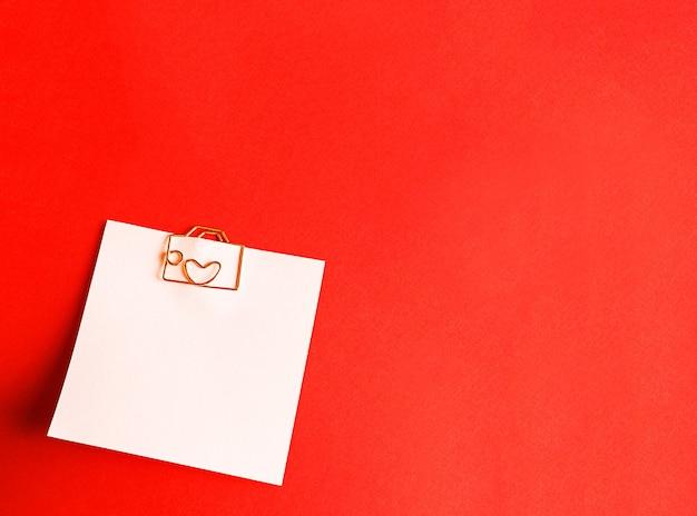 Vierkant blad voor aantekeningen met een paperclip in de vorm van een letter en een hart
