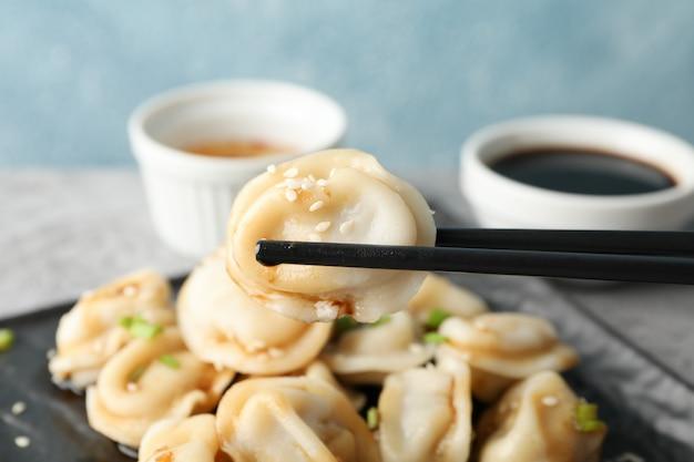 Vierkant bord met dumplings, sauzen en eetstokjes tegen blauw