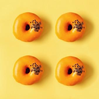 Vierkant gewas van zoete donut met oranje glazuur. de smakelijke doughnut op roze textuur, kopieert ruimte, hoogste mening