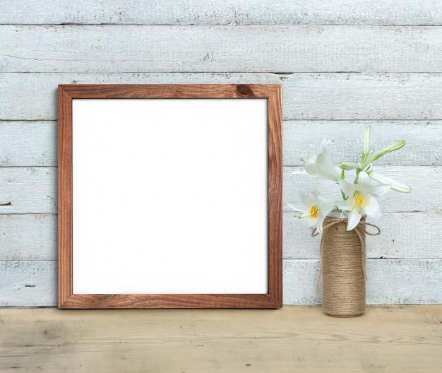 Vierkant oude houten frame in de buurt van een boeket van lelies staat op een houten tafel