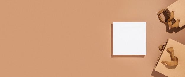 Vierkant podium voor presentatie, ambachtelijke verpakkingspakketten op een bruine kartonnen achtergrond. bovenaanzicht, plat gelegd. banier.