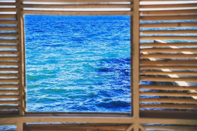 Vierkant raam met uitzicht op de klassieke blauwe zee en de blauwe lucht. houten frame.