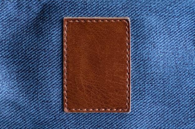 Vierkant stuk leer op de jeans genaaid. bruin leer. kopieer ruimte.
