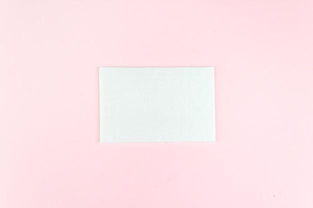 Vierkant uitnodigingskaartmodel op een zachtroze achtergrond. plat lag, bovenaanzicht, kopieer ruimte.