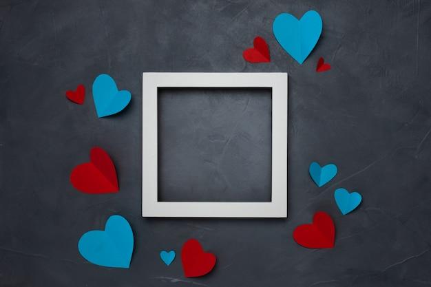 Vierkant wit leeg frame met hartjes op grijze gestructureerde achtergrond met copyspace