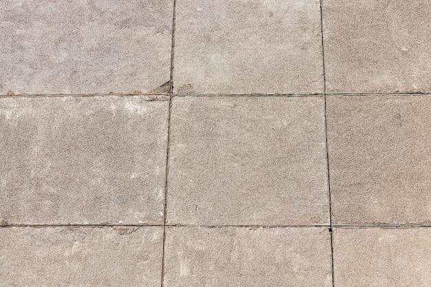 Vierkante betonnen platen, waarvan de muur van een gebouw met meerdere verdiepingen en de woning van mensen is gemaakt, close-up