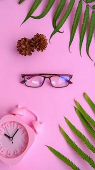 Vierkante bril op de foto in minimale zomerstijl op een pastelroze achtergrond.