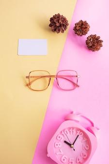 Vierkante bril op de foto in minimale zomerstijl op een pastelroze en gele achtergrond. wekker , pijnboombloemen , visitekaartjes