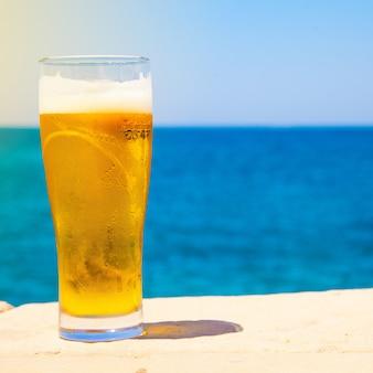 Vierkante foto van glas bier in de zomer in de buurt van zee