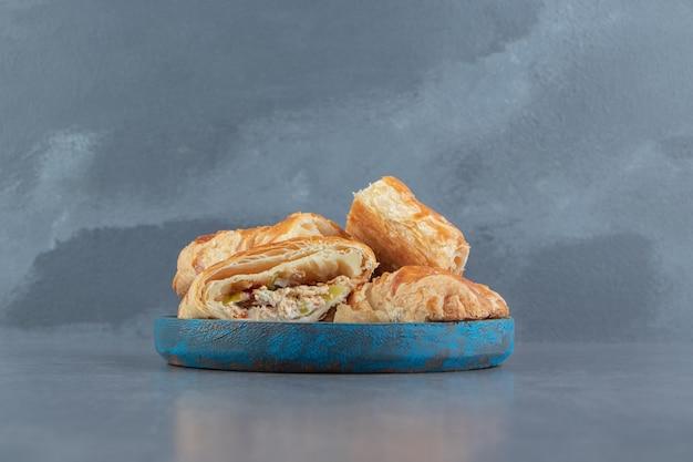 Vierkante gevulde gebakjes op blauw bord. Gratis Foto