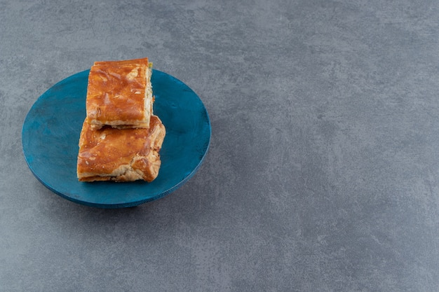 Vierkante gevulde gebakjes op blauw bord.