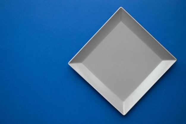 Vierkante grijze plaat op een blauwe tafel, bovenaanzicht