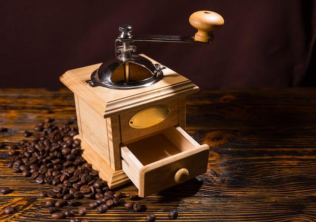 Vierkante houten koffiemolen met kleine open lade en metalen slinger boven tafel met donkere achtergrond en verspreide donkere bonen